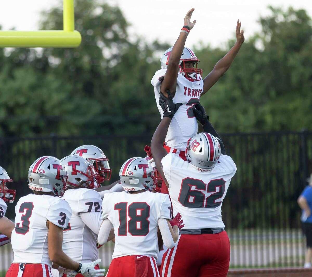 Travis quarterback Anthony Njoku (2) is lifted into the air by his teammates after he scores a touchdown during the first quarter of a non-district football game against Cypress Falls at Cy-Fair FCU Stadium, Saturday, Sept. 11, 2021, in Cypress.