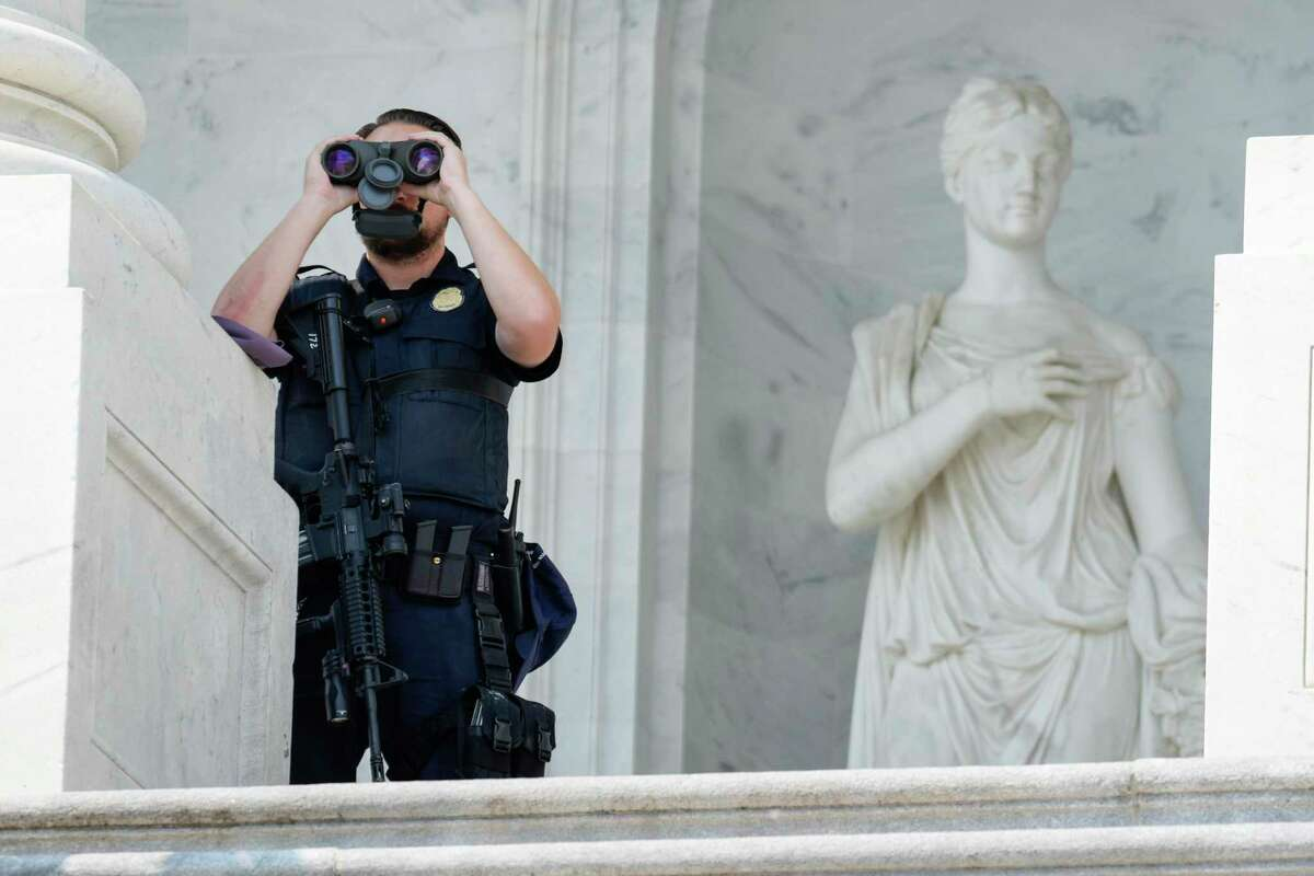 """WASHINGTON, DC - SEPTEMBER 13: A member of the U.S. Capitol Police uses binoculars at his post on the East Front of the U.S. Capitol on September 13, 2021 in Washington, DC. U.S. Capitol Police Chief J. Thomas told reporters after a classified briefing that temporary fencing around the Capitol Building would go up ahead of the Justice for J6"""" rally, which is expected to draw people calling on justice for those arrested after the violent insurrection on January 6th. (Photo by Drew Angerer/Getty Images)"""
