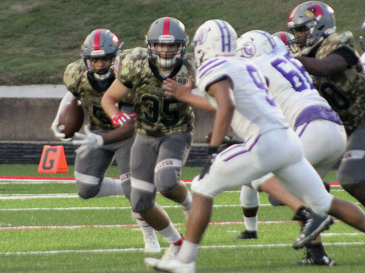 Alton's Keith Gilchrese (5) carries the ball last week against Collinsville at Public School Stadium.