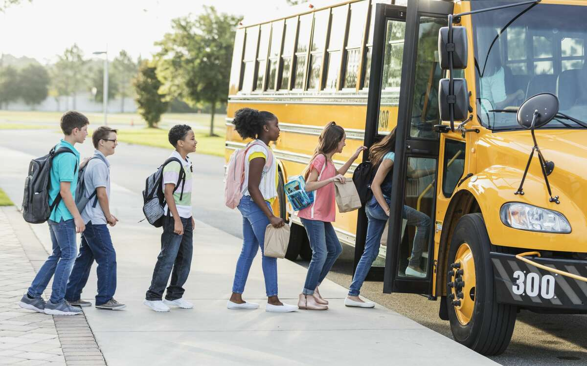 A group of six middle school students, 11 to 13 years old, boarding a school bus.