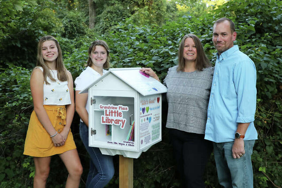 Annie Bozarth, a freshman at Edwardsville High, poses with the Little Library she and her stepfather, Wayne Downing, mother, Allison, and sister Elle built.