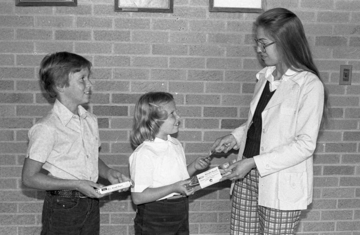 Almost 2,000 pounds of chocolate mints and almond bars are planned to be sold by Manistee Catholic Central third, fourth, fifth and sixth graders beginning today. The students will be selling the candy in the area at a price of $1 each, with proceeds going to the school's English program. Troy Bialik (left), an MCC fifth grader, and Jennifer Nowak, a third grader, make their first sale to Maria Hermann (right). The photo was published in the News Advocate on Sept. 18, 1981.