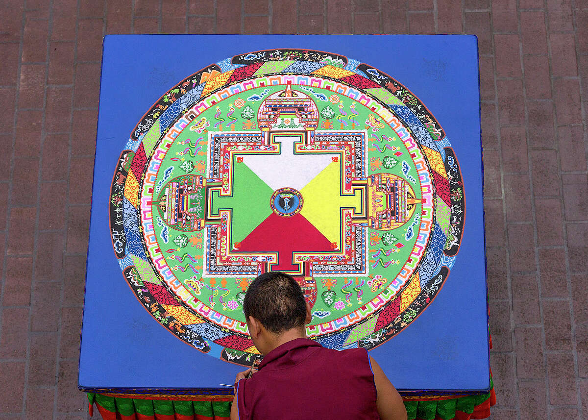 """A monk from the Gaden Shartse Norling Monastery in Mundgod, India, completes a sacred sand mandala. The monastery's """"Sacred Arts of Tibet"""" tour stops at University of Houston-Clear Lake Sept. 27 through Oct. 1. Learn more at https://events.uhcl.edu/index.php?eID=3766."""