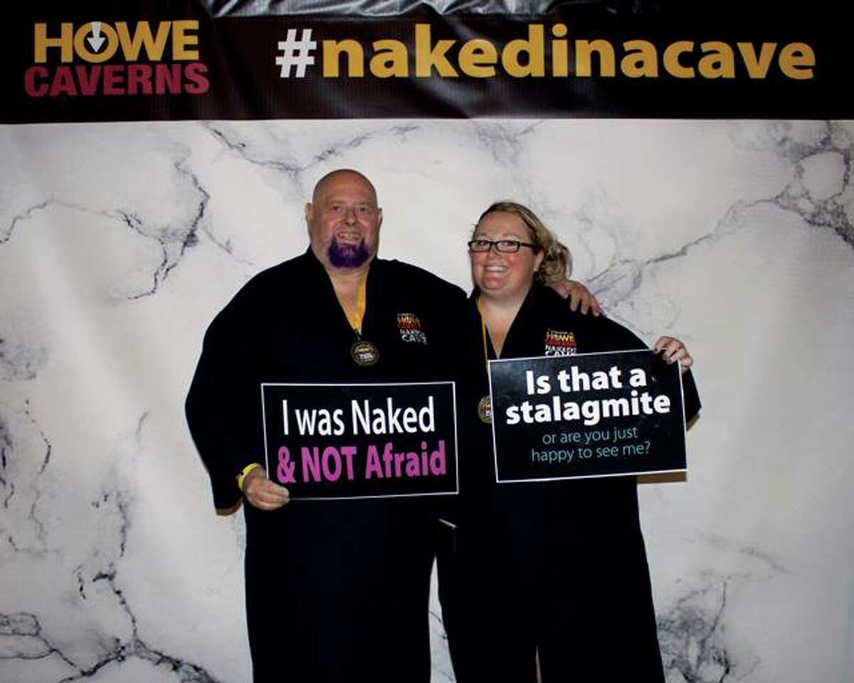 A couple poses for a photo at the Naked in a Cave event at Howe Caverns.