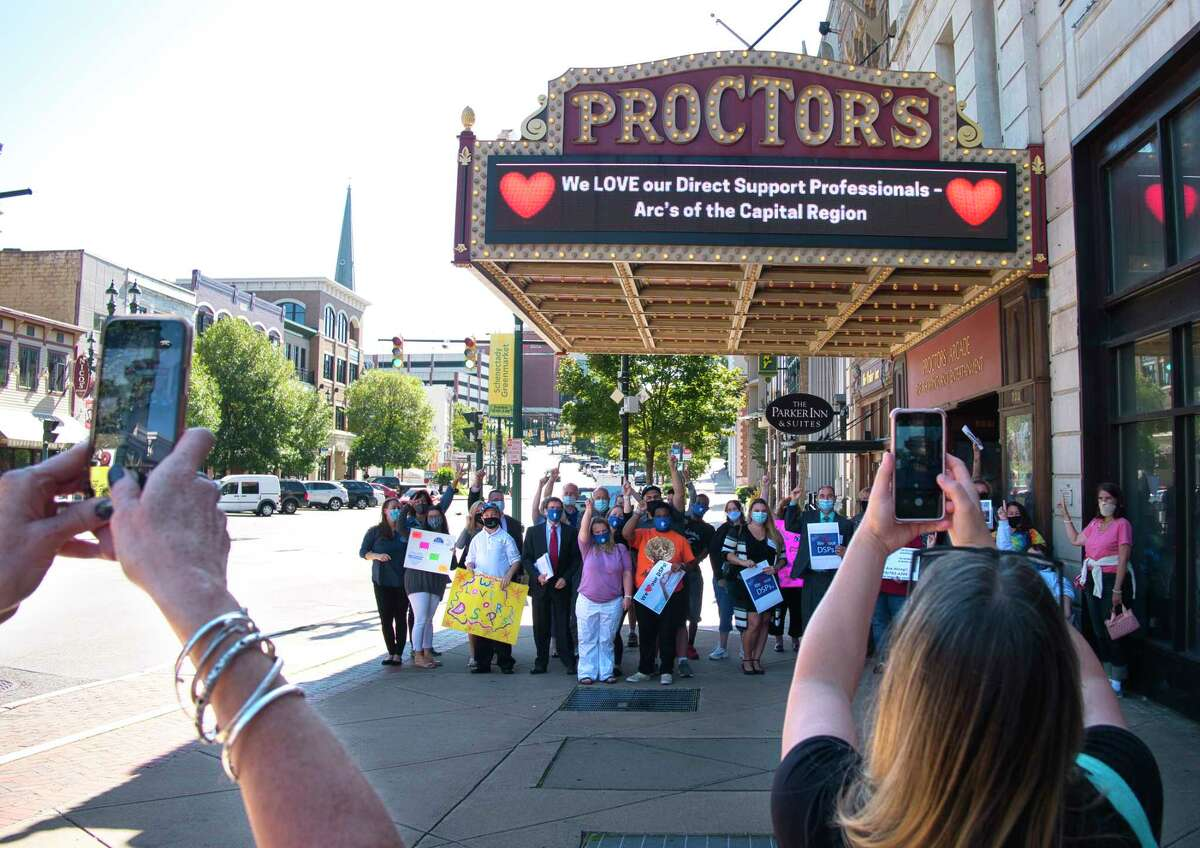 ARC direct support professionals, individuals and families receiving services from ARC pose under the Proctors marquee following a press event at Proctors on Thursday, Sept. 16, 2021, in Schenectady, N.Y.