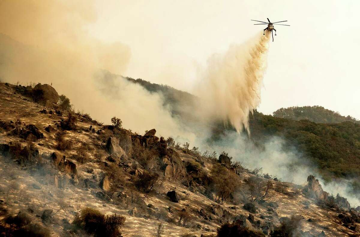 This file photograph shows a helicopter dropping water on the KNP Complex burning along Generals Highway in Sequoia National Park on Sept. 15.