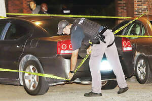 An Alton Police oficer adjusts the crime scene tape around a car early Sept. 9 at the end of the cul-de-sac for Oakwood 700 in the Oakwood Estates housing complex following an incident in which three people were shot.