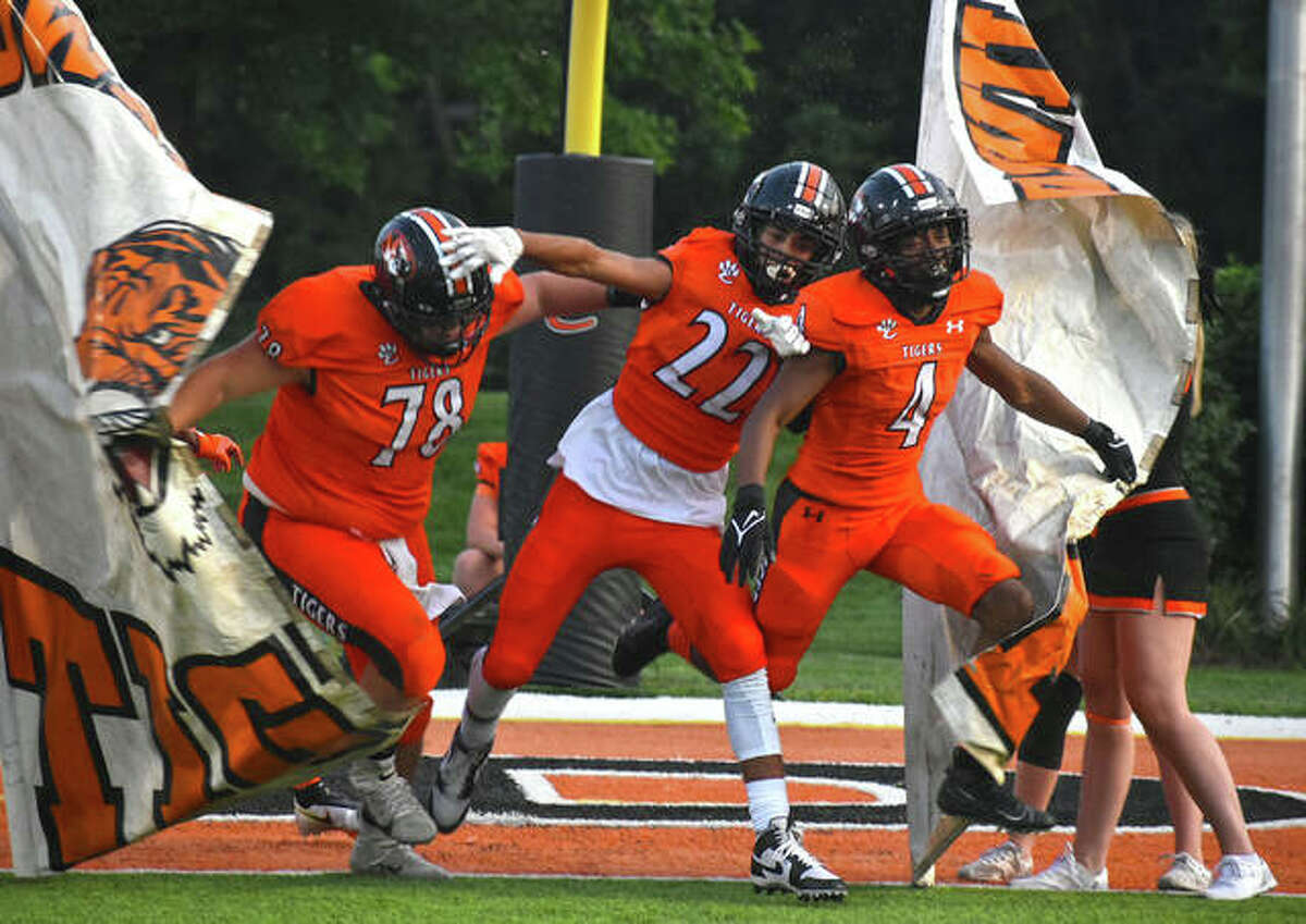 Edwardsville's Dawson Rull, left, Kareem Haroun, center, and Kellen Brnfre break through the banner to lead the team onto the field for the Week 3 home opener against Champaign Central on Friday inside the District 7 Sports Complex.