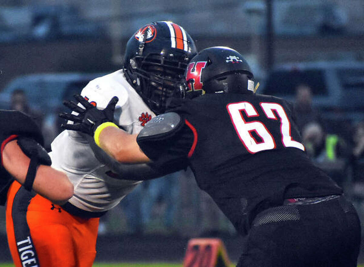 Edwardsville's Nasim Cairo, left, attempts to fight through a block from a Highland offensive lineman during Week 2 in Highland.