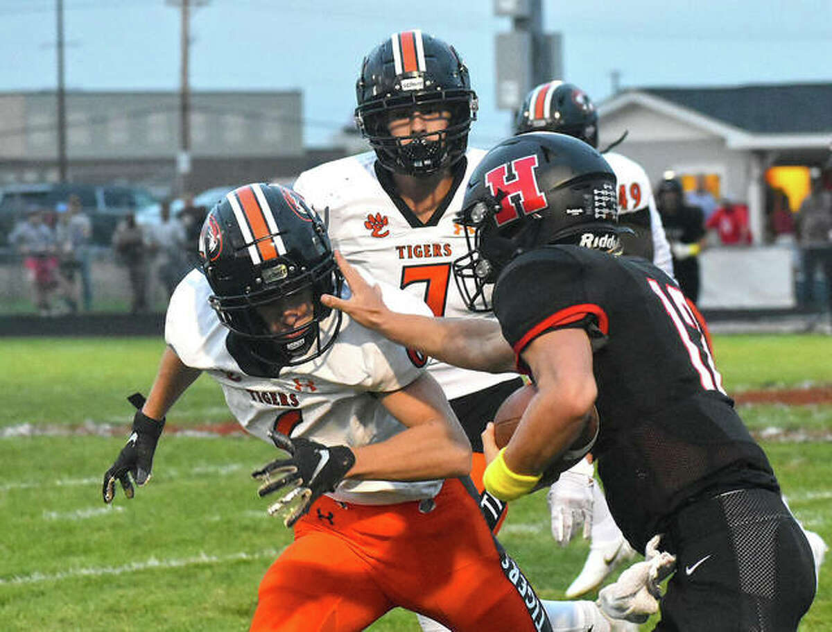 Edwardsville's Carter Knyole, left, attempts to bring down the Highland ball carrier during Week 2. Also pictured for EHS is Chase Parker.