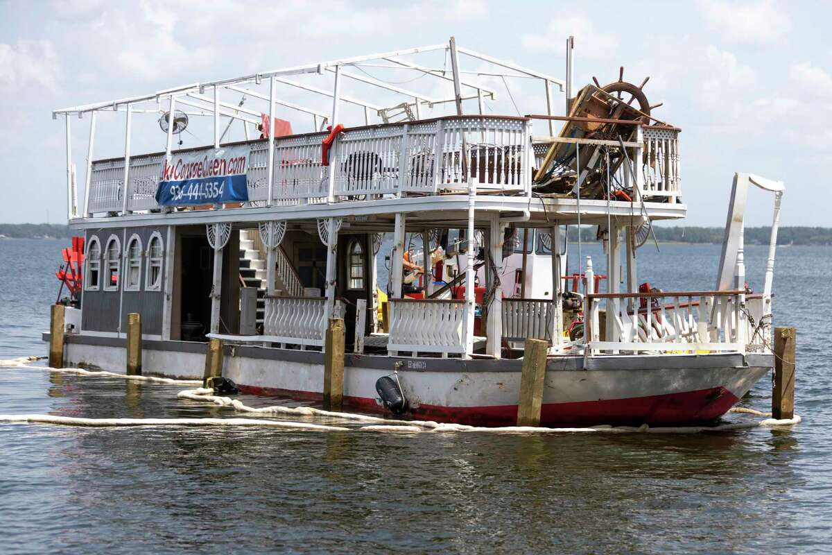 The Lake Conroe Queen is seen being hitched to the back of a tow boat by Lewis Towing & Salvage, Friday, Aug. 20, 2021, in Lake Conroe. The Lake Conroe Queen capsized in mid-August near Regency Point during a thunderstorm.