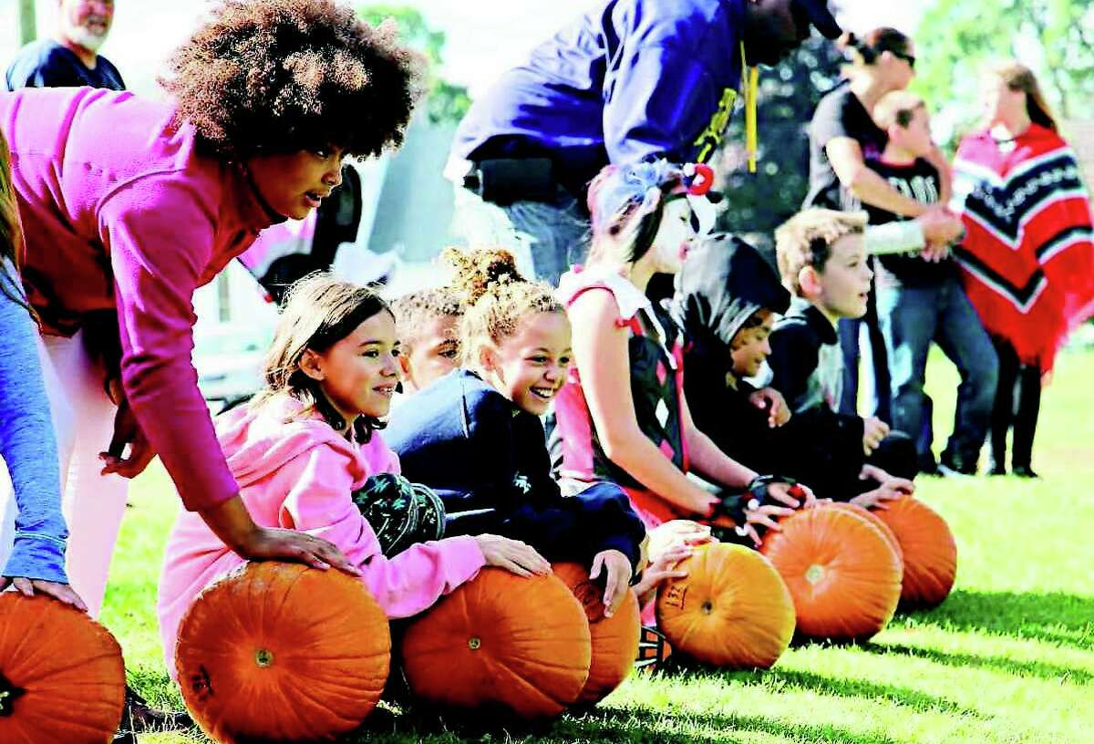 A group of pumpkin-rollers wait for the signal to shove their pumpkins down the hill at the Caseville County Park during the city's 2018 Pumpkin Festival. The object of the competition was to see who could get their pumpkin to roll the farthest.