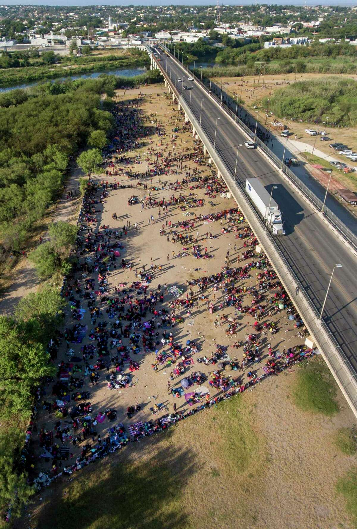 Migrants pass back-and-forth on a weir dam on the Rio Grande Thursday from Ciudad Acuña, Mexico, into Del Rio, Texas, right, as they wait to be processed by immigration officials under the nearby international bridge between the two cities. Thousands of migrants are waiting at the bridge to be processed by the Border Patrol