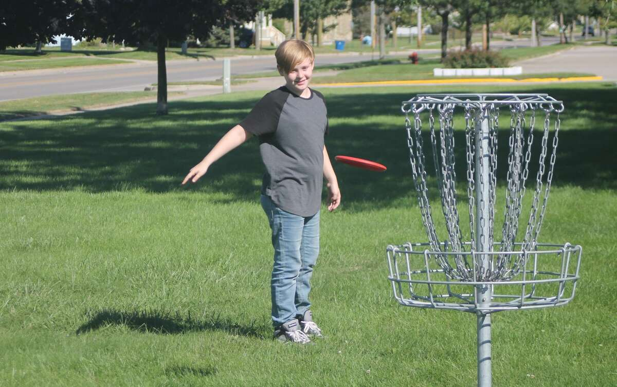 An Armory Youth Project student tosses a disc at the basket during the first day of the Armory's disc golf program in Manistee on Wednesday.