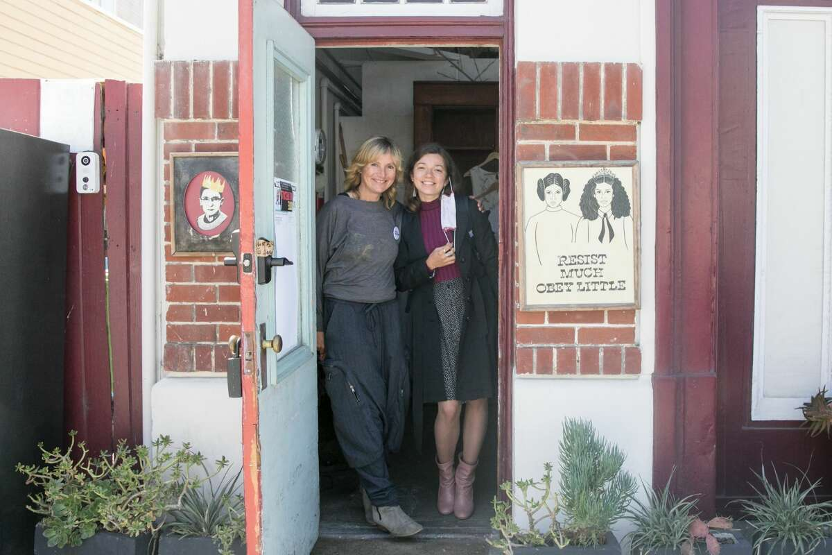 """Carolin Hagenstroem, left, and Anastasia Podvysotska, right, stand in the doorway of Engine 43 art studio, otherwise known as Mia Thermopolis' house in """"The Princess Diaries,"""" which is located in the Excelsior District of San Francisco, on Sept. 15, 2021."""