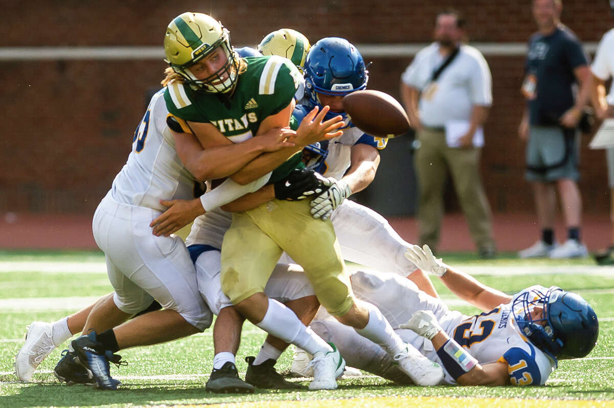 Midland High's defense forces a fumble during an Aug. 26, 2021 game against Traverse City West at Michigan Stadium in Ann Arbor.