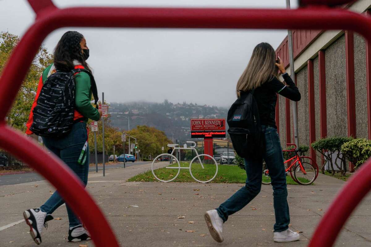 Students arrive at John F. Kennedy High School in Richmond on Tuesday. The Contra Costa County district that includes the school is considering mandating vaccines for eligible children.
