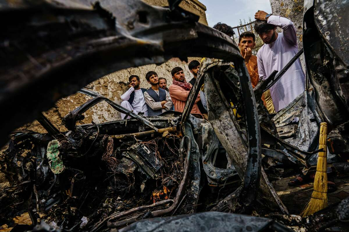 Relatives and neighbors of the Ahmadi family gathered around the incinerated husk of a vehicle that the family says was hit by a U.S. drone strike, in Kabul, Afghanistan, Monday, Aug. 30, 2021. (Marcus Yam/Los Angeles Times/TNS)