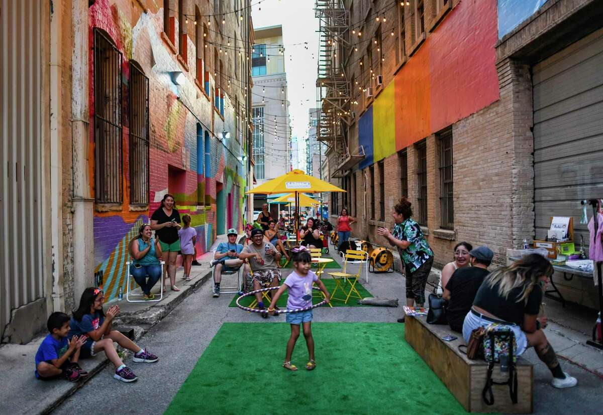 Children enjoy a hula hoop at Peacock Alley, the downtown San Antonio hotspot between 110 and 118 Broadway that showcases Instagram-worthy backdrops, on Friday, June 18, 2021.
