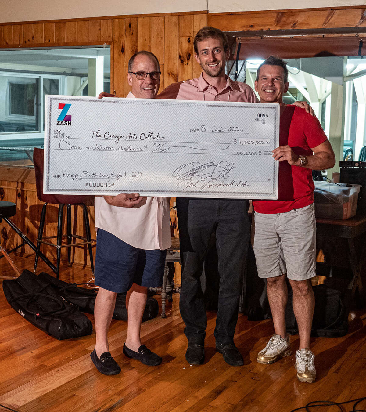 $1 million check presented to Kyle Barrett Price, center, by Ted Farnsworth,left, and Rod Vanderbilt. (Photo by Paul Valovic)
