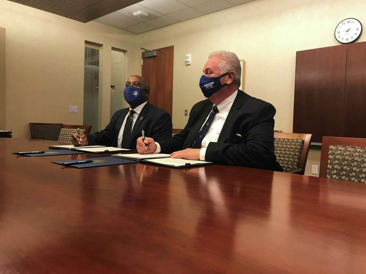 """Gateway Community College CEO William """"Terry"""" Brown and University of New Haven Interim Provost Mario Gaboury sign an agreement between the two institutions at Gateway Community College Sept. 16, 2021."""