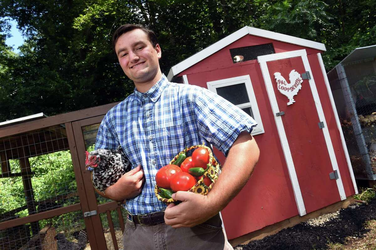 Dominick Lombardi is photographed holding a Speckled Sussex chicken and a basket of tomatoes and peppers at his backyard farm in Orange, which he informally calls, Hollow Farm, on Sept. 3, 2021.