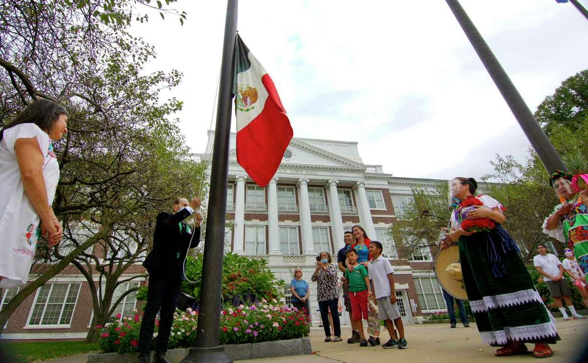 Leon Cio Flores Velasco raises the Mexican flag during a ceremony to celebrate Mexican Independence Day at Town Hall in Greenwich, Conn., on Thursday, September 16, 2021.