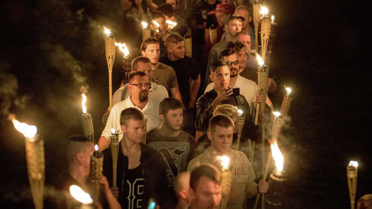 """Chanting """"White lives matter,"""" """"You will not replace us"""" and """"Jews will not replace us,"""" several hundred white nationalists and white supremacists carrying torches march in Charlottesville on Aug. 11, 2017, during the Unite the Right Rally. Photo for The Washington Post by Evelyn Hockstein"""