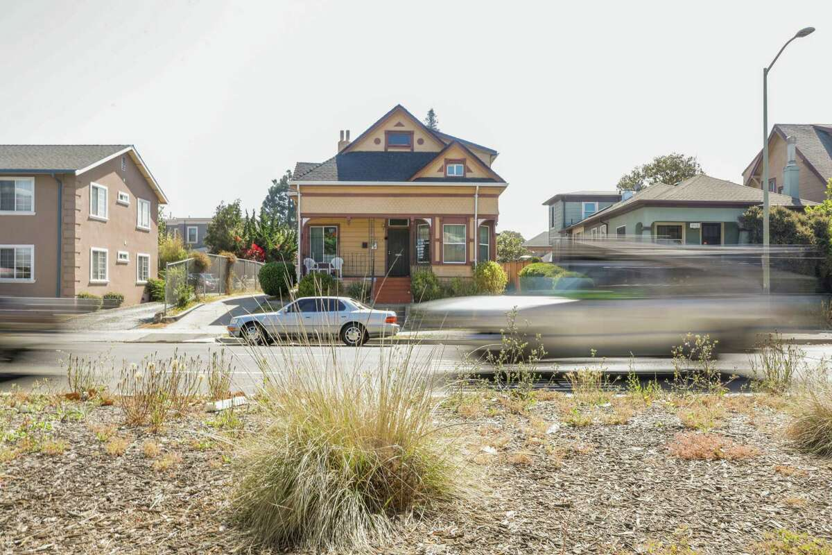 Cars pass by a duplex in Oakland. SB9, which Gov. Gavin Newsom signed Thursday, would make it easier to split lots and convert homes into duplexes.