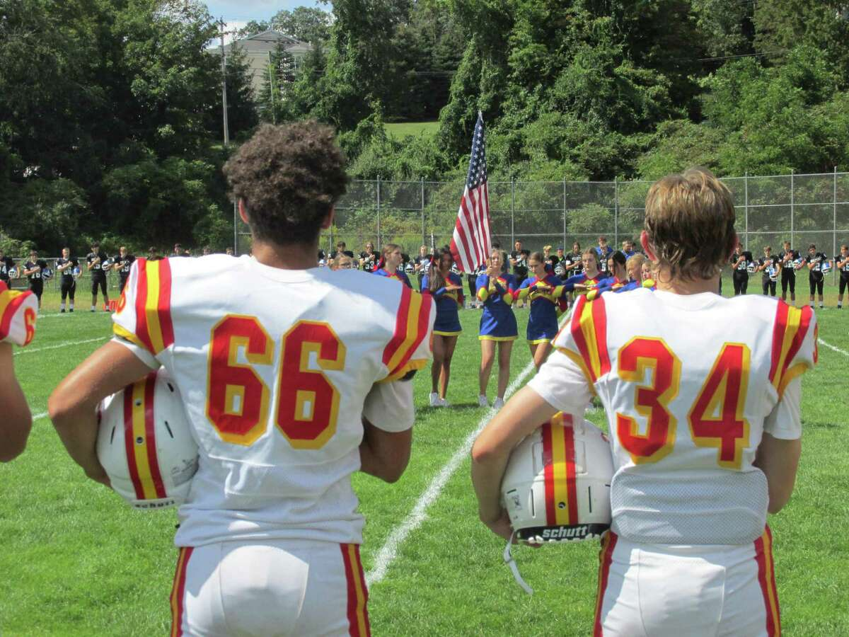 A pair of players from the Gilbert/Northwestern/Housatonic co-op footbal lteam stand at attention during the national anthem before a recent game.