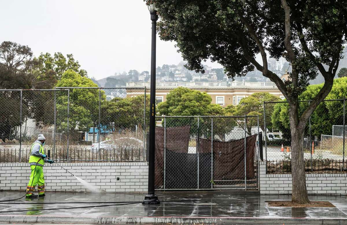 A sanitation worker power-washes the sidewalk next to the empty lot at 730 Stanyan St. in the Haight.