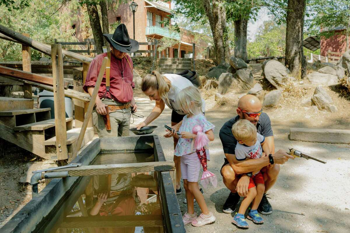 A family pans for gold at California's Columbia State Historic Park, Aug. 24, 2021. A writer went searching for Asian American history in the foothills of the Sierra Nevada, where thousands of Chinese immigrants labored during the Gold Rush but where traces of their presence are few.