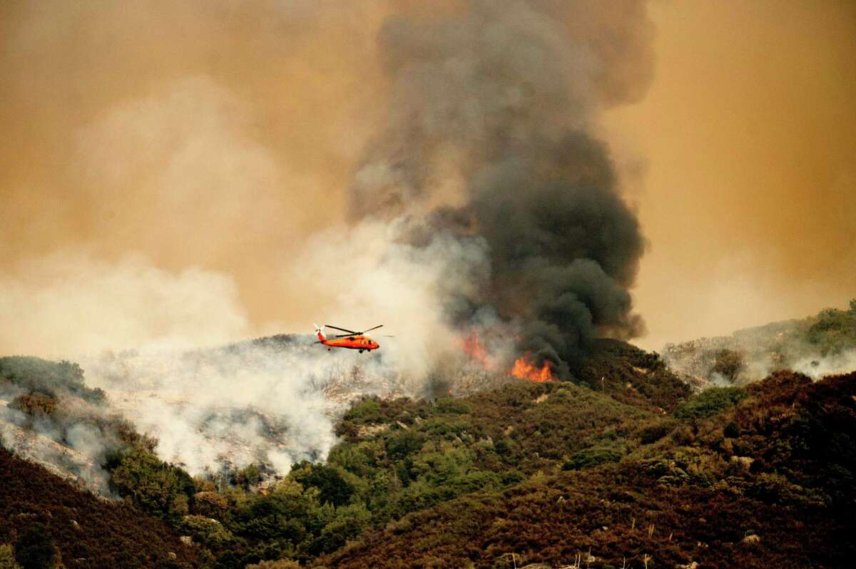 A helicopter prepares to drop water on the KNP Complex wildfire in Sequoia National Park.
