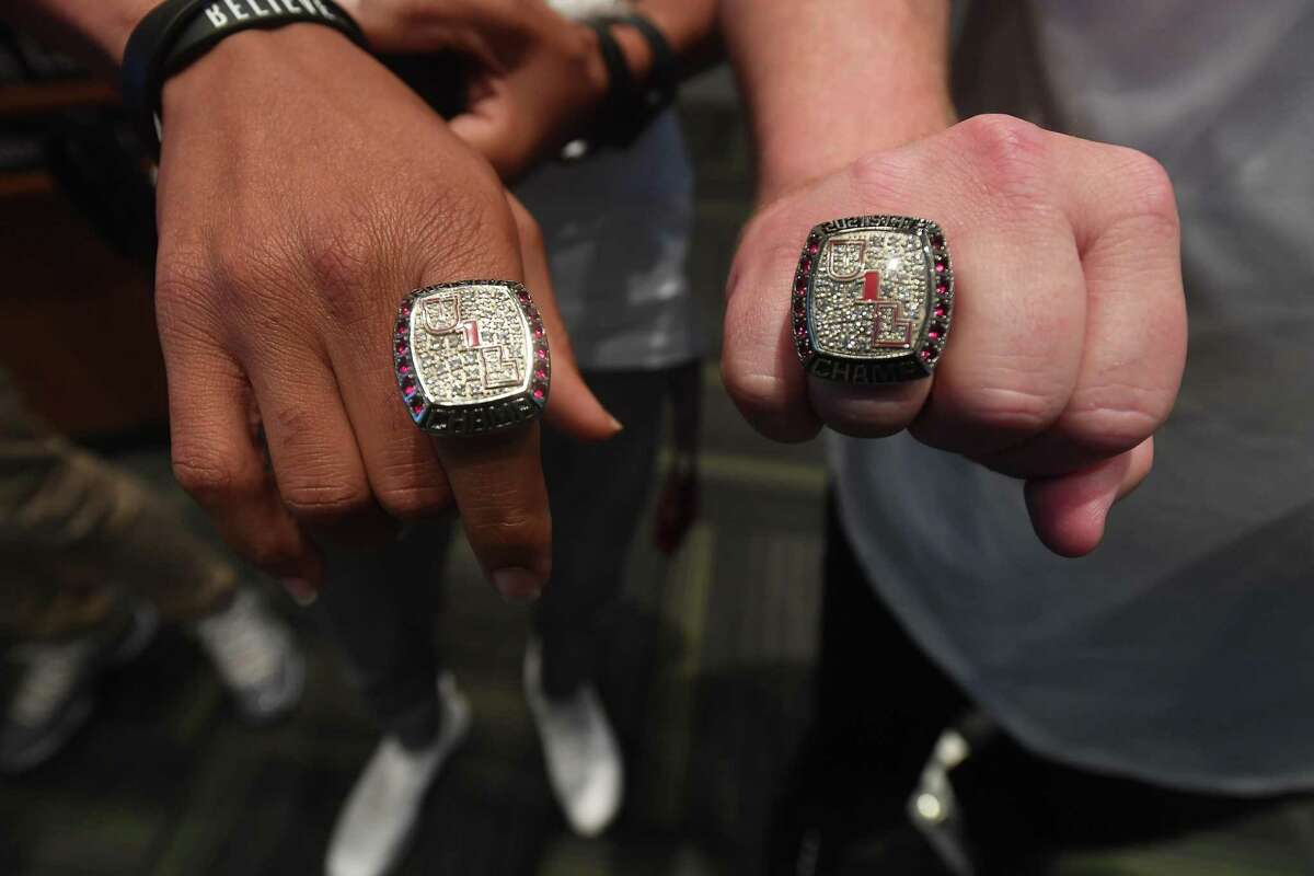 Coaches show off their newly won bling during a state champion ring presentation for Port Arthur Memorial track and field stand-outs Tre'Vonte Caines and Maleek Jones and coaches at the Port Arthur school board meeting Thursday. Photo made Thursday, September 16, 2021 Kim Brent/The Enterprise