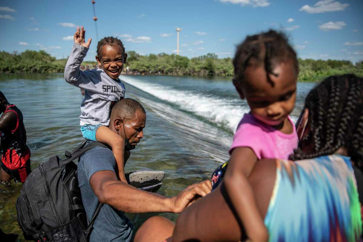 Migrants cross the Rio Grande in Ciudad Acuna, Mexico, on Thursday, Sept. 16, 2021. Thousands of migrants, mostly from Haiti, have arrived in the area, resulting in a population surge in Del Rio. Texas.