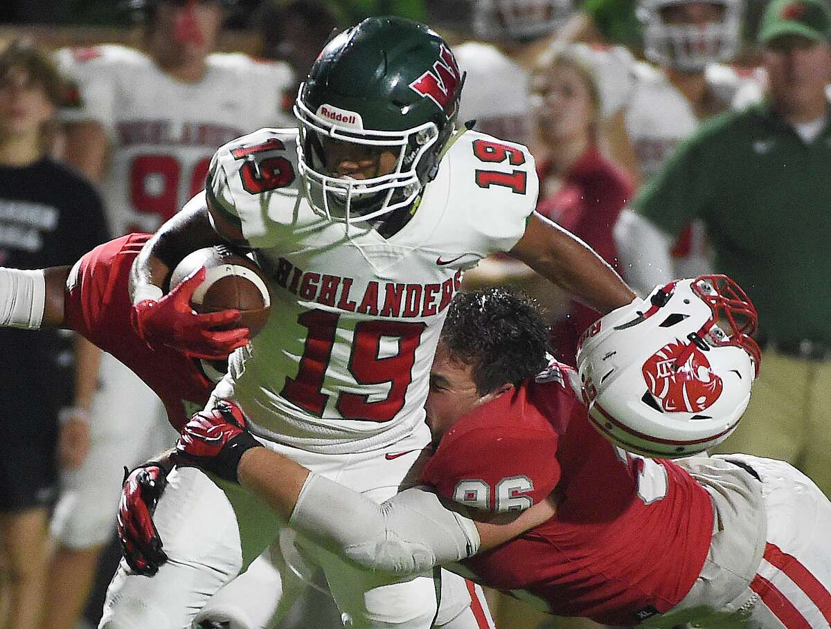 The Woodlands wide receiver Jason Williams (19) is tackled by Katy defensive lineman Dylan Bennett during the second half of a high school football game, Thursday, Sept. 16, 2020, in Katy.