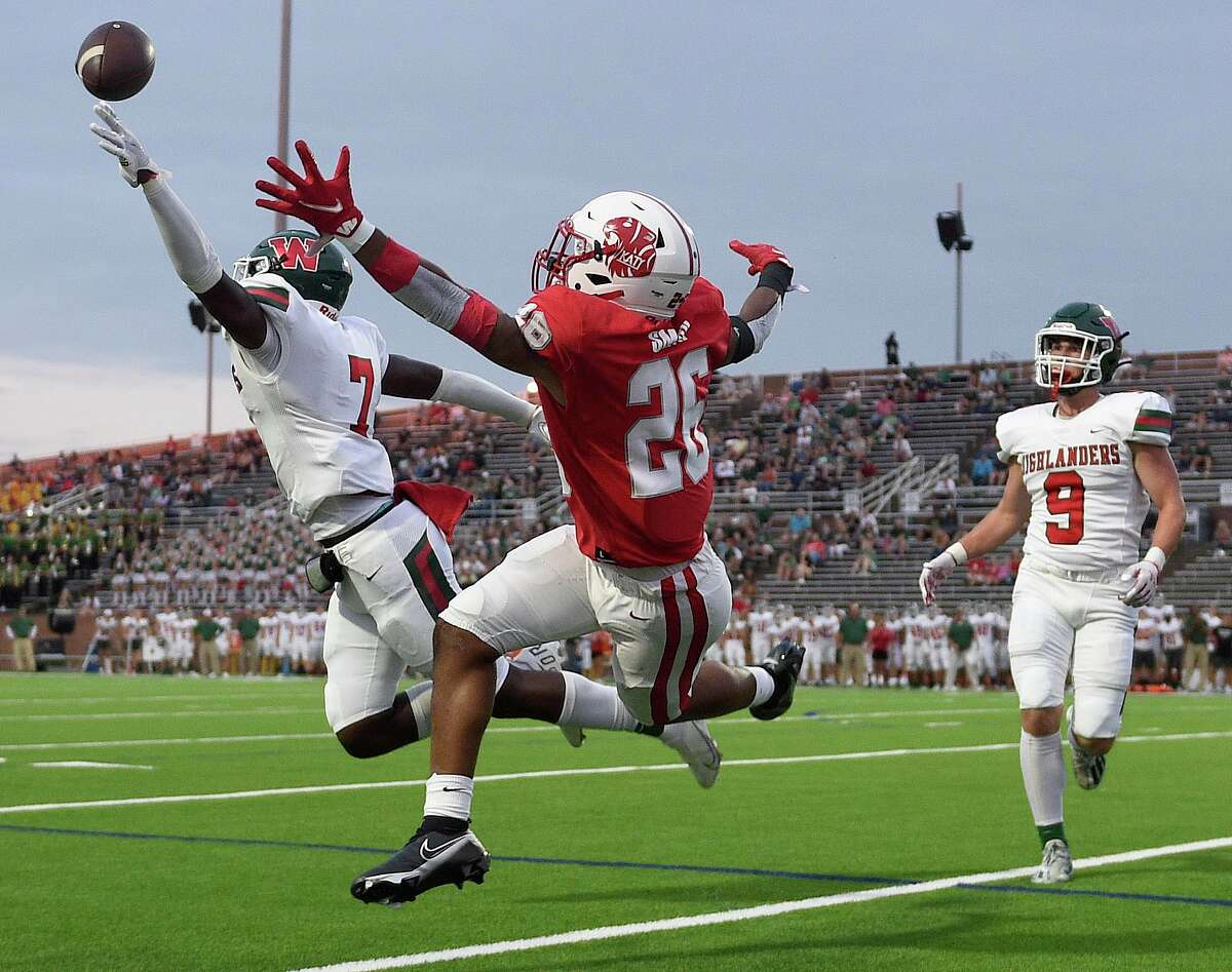 The Woodlands linebacker Martrell Harris, left, breaks up a pass intended for Katy running back Isaiah Smith (26) during the first half of a high school football game, Thursday, Sept. 16, 2021, in Katy.