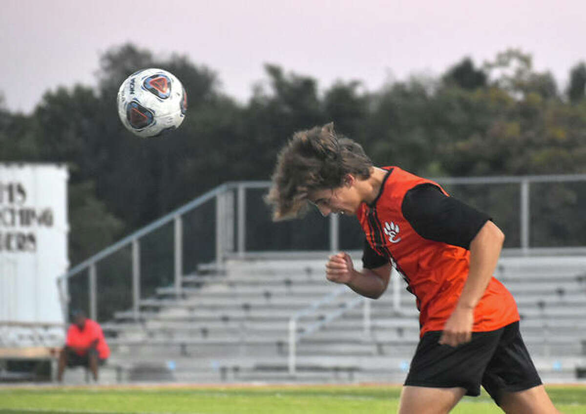 Edwardsville defender Jake Duboise heads a ball up the field against Belleville West during the first half on Thursday inside the District 7 Sports Complex.