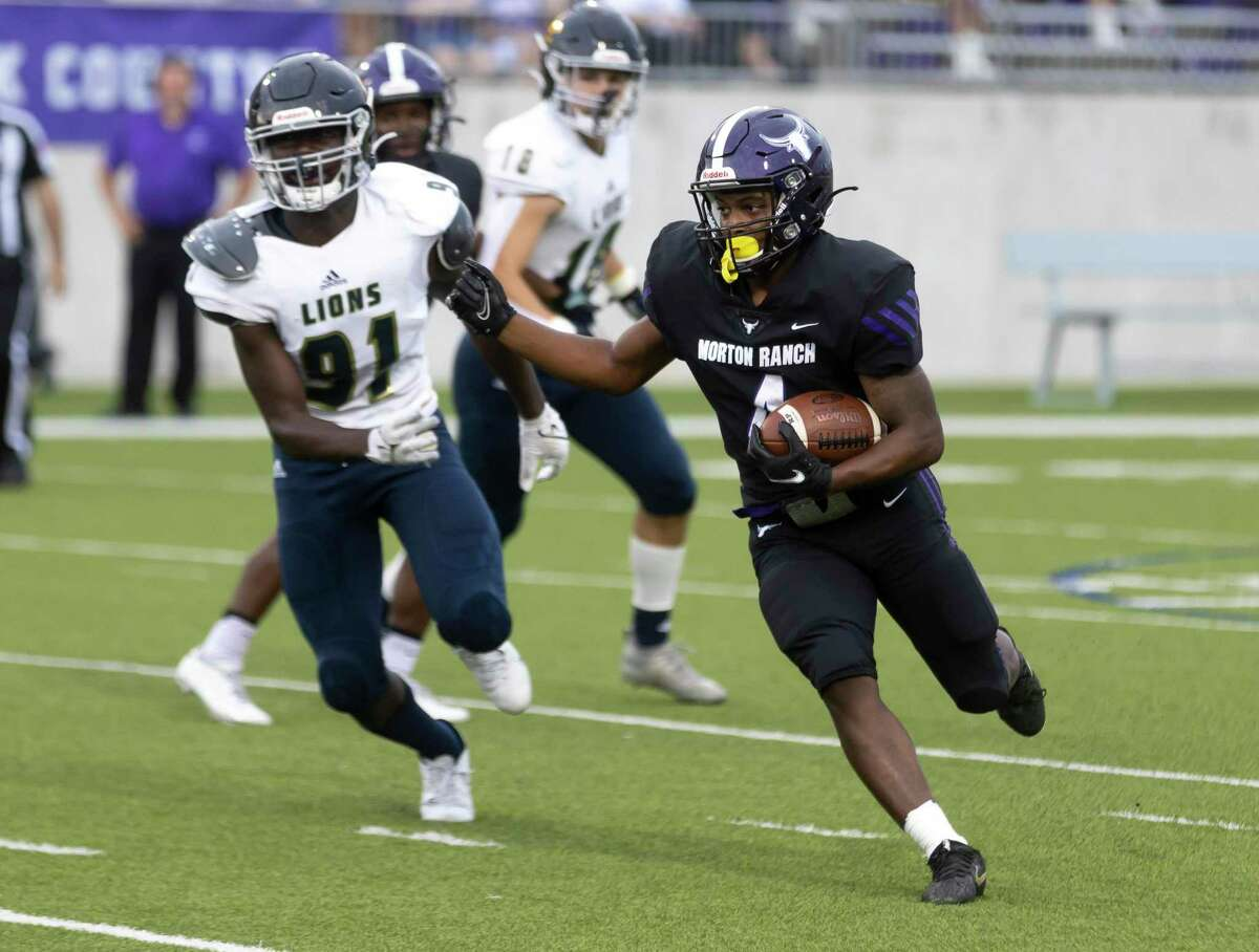 Morton Ranch running back Karsten Christopher (4) runs the ball while under pressure from Lake Creek defensive lineman Katey Adodoadji (91) during the first quarter of a a non-district football game at Legacy Stadium, Thursday, Sept. 16, 2021, in Katy.