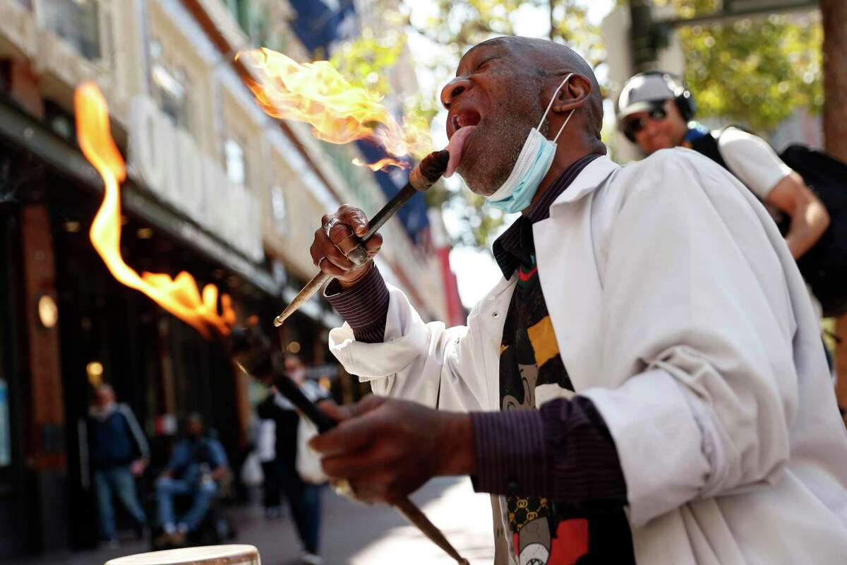 Larry Hunt, the San Francisco Bucket Man, plays his music with flaming drumsticks on Market Street.