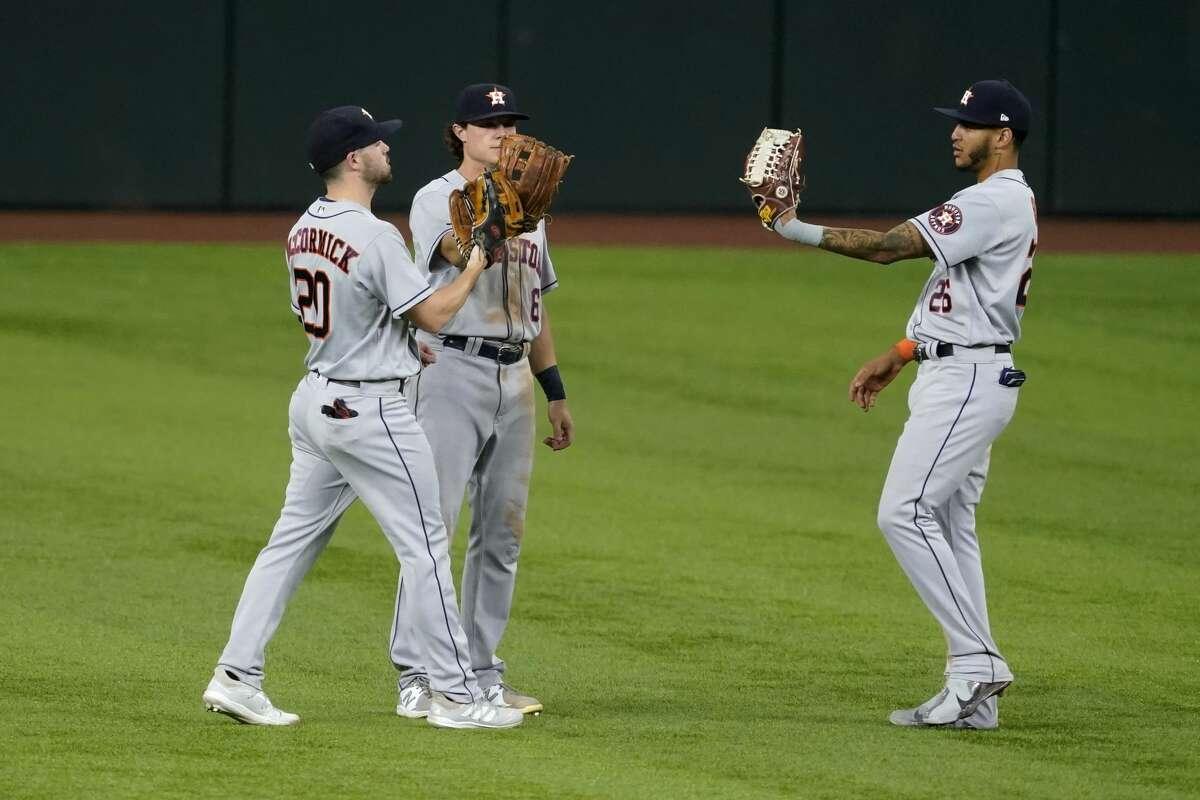 Houston Astros' Chas McCormick (20), Jake Meyers and Jose Siri (26) celebrate the team's 12-1 win in a baseball game against the Texas Rangers in Arlington, Texas, Thursday, Sept. 16, 2021. (AP Photo/Tony Gutierrez)