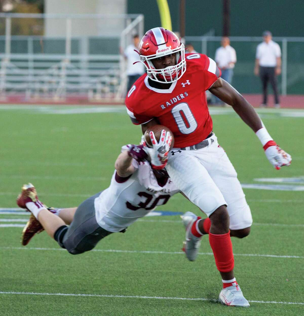 Taft running back, TJ Andrews carries the ball as Ben Klar, from Marshall, attempts to tackle him. Taft won 41-21.