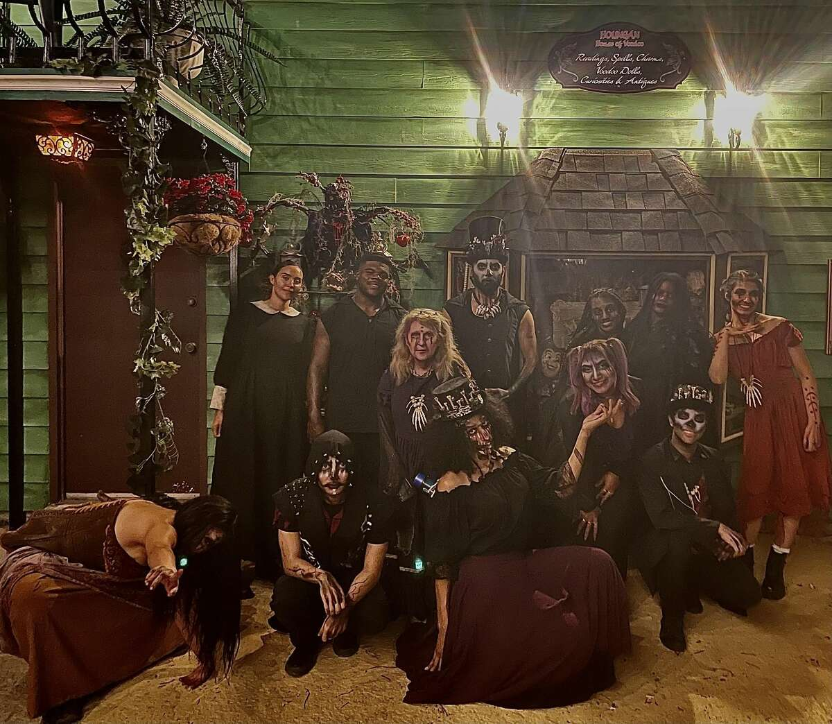 """Eddy Martinez (bottom left) with other scare actors pose at the new Six Flags haunted house called """"The Houngan House of Voodoo."""""""