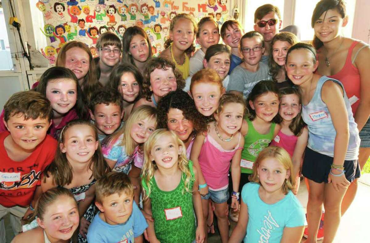 """In the center of these children, members of the """"Sugar Free Gang"""", is Joanne DeNovio, RN, C.D.E., who runs the group sponsored by Ellis Medicine. The children are members of this support group that assists children and families with diabetes. DeNovio, a diabetes educator, administers the group, the only one of it's kind in the Northeast, that holds year-round activities, a summer camp and boasts a list of impressive celebrity guest speakers who come to encourage the kids and their families. The kids gathered around DeNovio during the """"Sugar Free Gang's"""" annual picnic, at the Clifton Park Elks Lodge on Wednesday, Sept. 1, 2010, in Clifton Park, NY. On this night, Carling Coffing, a 24 year old professional golfer, in town for the Futures Golf Tournament, was on hand to speak to the families about how she deals with her Type 1 Diabetes, as an athlete and as a member of her family. (Luanne M. Ferris / Times Union )"""