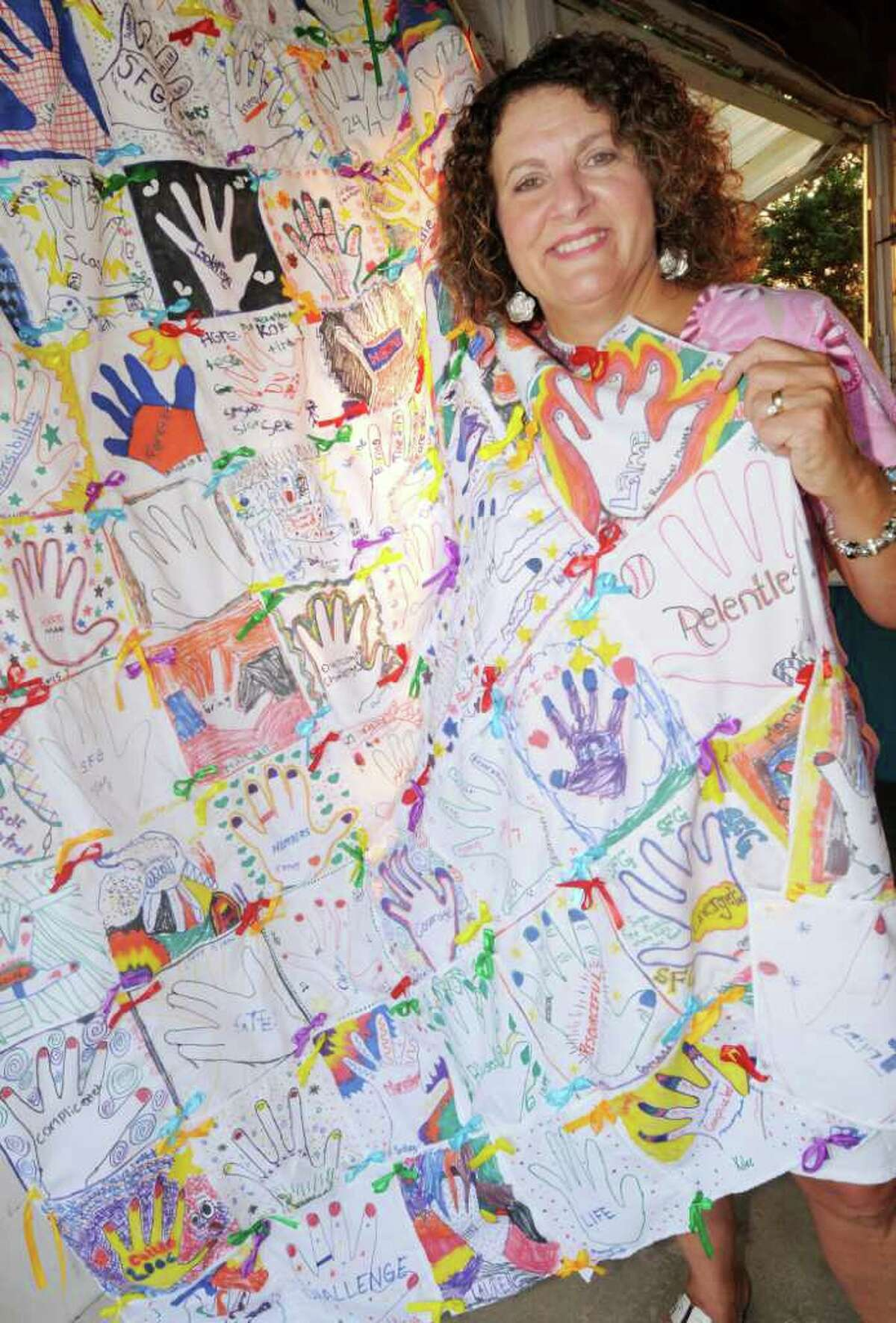 """Holding a quilt of hand prints made by members of the """"Sugar Free Gang"""", is Joanne DeNovio. (Luanne M. Ferris / Times Union )"""