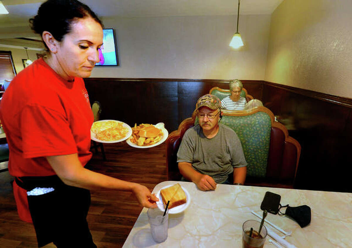 Red Apple Family Restaurant server Lumka Alimi gives an order to Jason Albert, of Troy, during lunchtime Thursday.