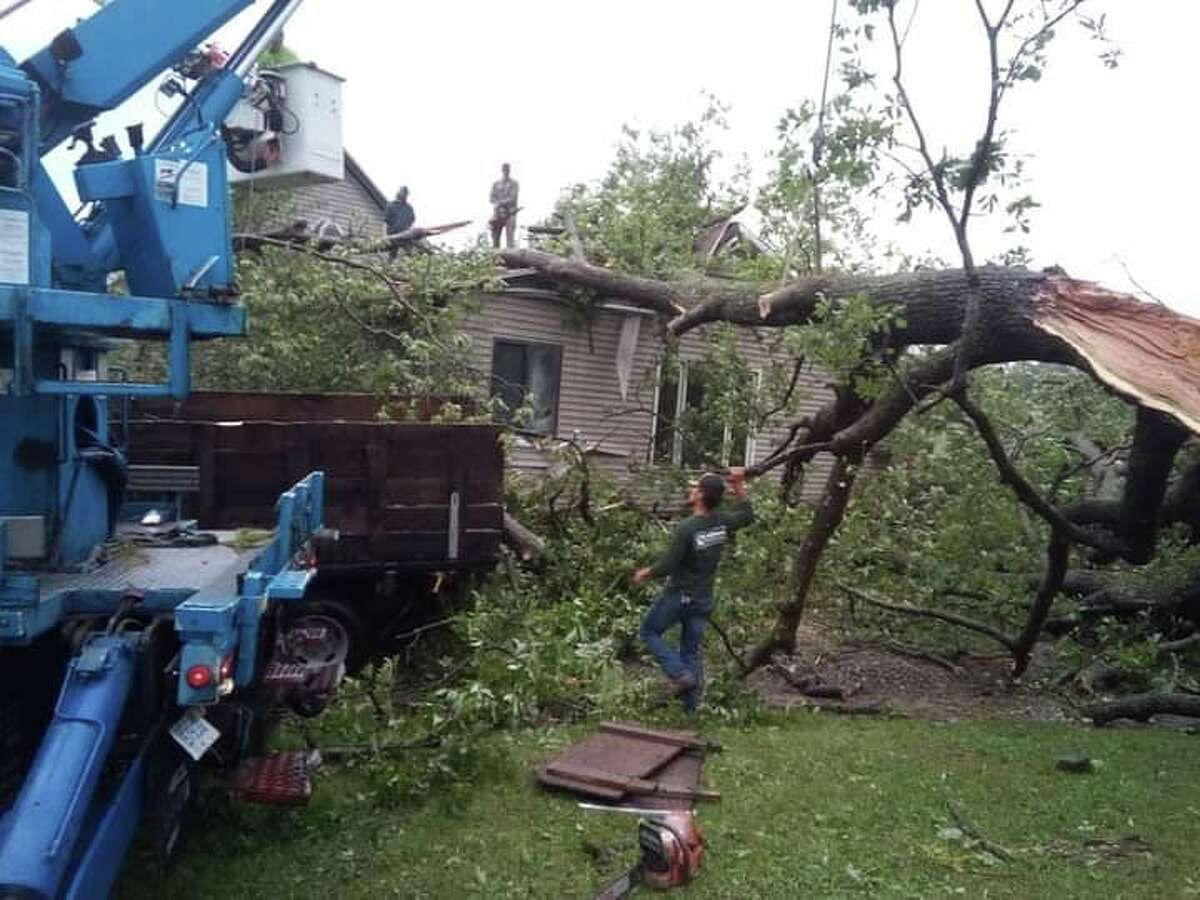 The family of Cathy and Alan Kerns wasted no time in helping to remove a huge oak tree which crashed through the roof and ceiling of their home. (Courtesy photo)