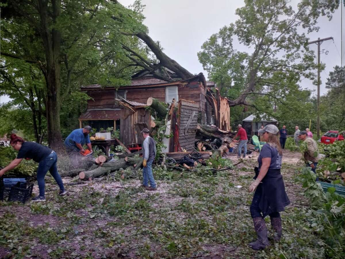 Neighbors and friends gathered at the Tiki Hut in Chase right after the storm, to help clean up damage where a large maple crashed through the roof on a home on the property. (Star photo/Shanna Avery)