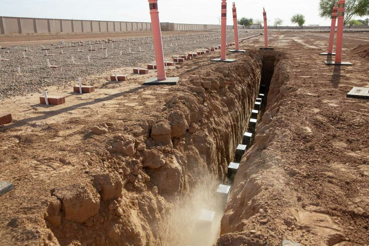 Urns containing the cremated remains of 13 Maricopa County residents are placed in their resting place at White Tanks Cemetery.