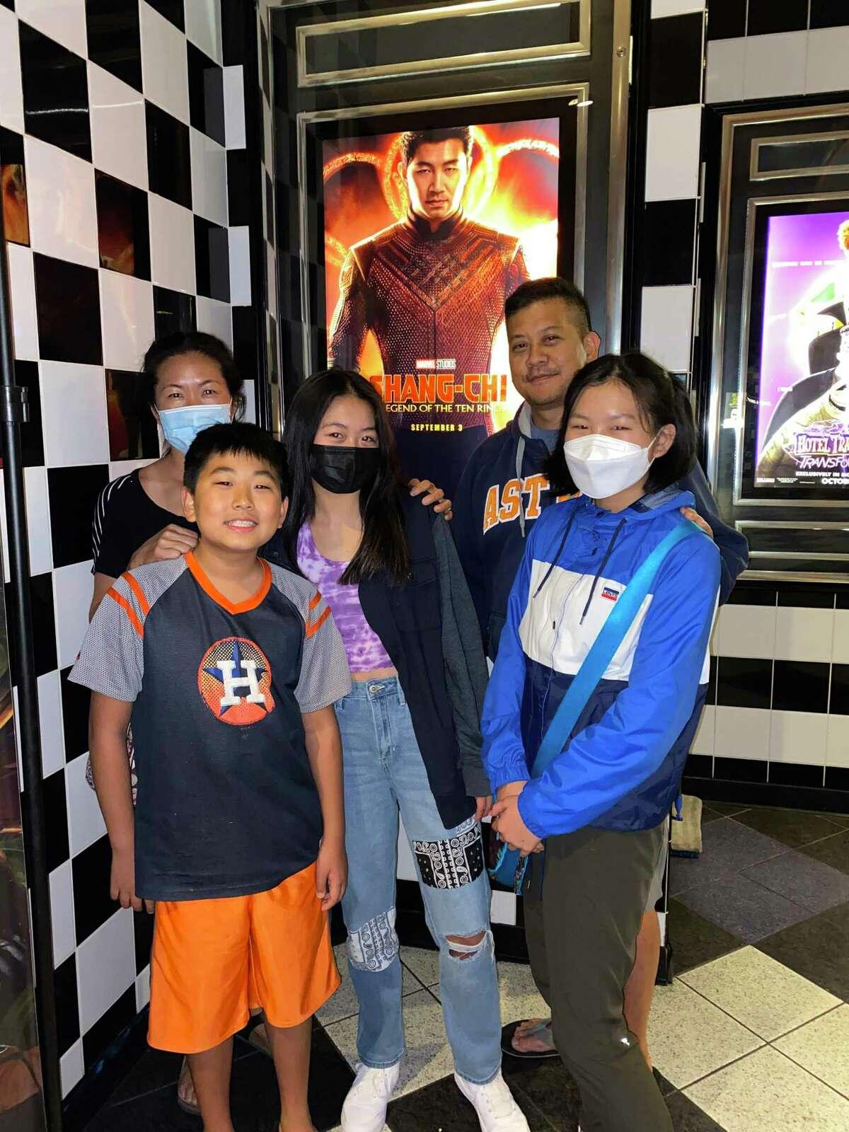 Harold Yi, Christina Yi, Joanne Yi, Eunice Yi, and Joshua Yi pose in front of a movie poster after they saw Shang-Chi.